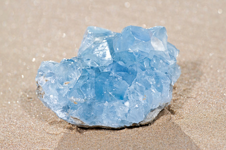 Blue Celestite cluster from Madagascar lying on wet sand on the beach at sunrise. Stock Photo