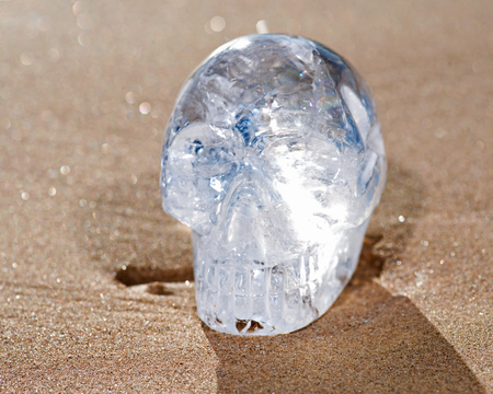 Clear Quartz Carved  Crystal Skull on the beach at the sunrise in front of the lake.