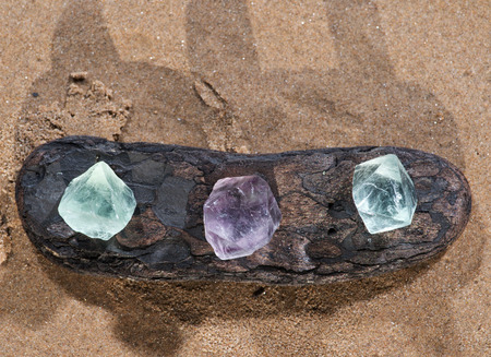 Purple and Green Fluorite Natural Octahedron Crystals on the beach at sunrise. Foto de archivo