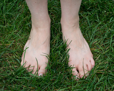 Woman standing on the grass with bare feet. Walking barefoot. Grounding.