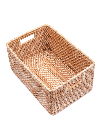 Handwoven in Indonesia exotic and functional rattan storage basket isolated on white background.