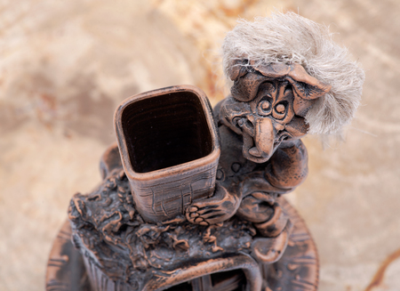 Old smiling witch sitting on the chimney and petrified wood background Banque d'images