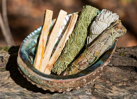Smudge kit - Palo Santo sticks, Wildcrafted dried white sage (Salvia apiana), Mugwort (Artemisia vulgaris), and Siskiyou Cedar (Chamaecyparis lawsoniana) wrapped in organic hemp twine, Abalone shell. 免版税图像 - 112186560