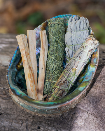 Smudge kit - Palo Santo sticks, Wildcrafted dried white sage (Salvia apiana), Mugwort (Artemisia vulgaris), and Siskiyou Cedar (Chamaecyparis lawsoniana) wrapped in organic hemp twine, Abalone shell. 免版税图像 - 112186735