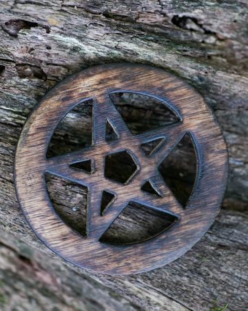 Hölzernes eingekreistes Pentagrammsymbol auf faseriger Baumrinde im Wald. Fünf Elemente: Erde, Wasser, Luft, Feuer, Geist.