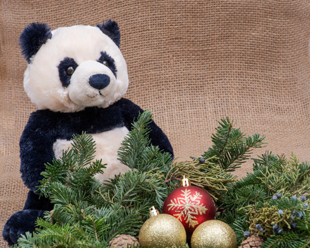 Winter holiday decoration: fraser fir table wreath centerpiece with cones, juniper, Christmas tree balls and panda bear stuffed plush toy on burlap background