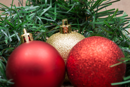 Winter holiday decoration:  green garland and Christas tree balls on burlap background