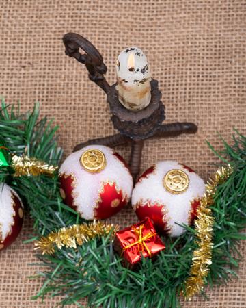 Winter holiday decoration: Christmas tree balls, gift decor, tinsel garland and burning candle burlap background Imagens