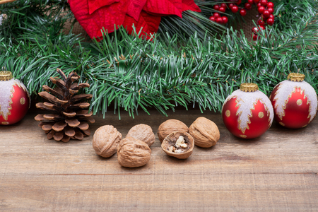 Winter holiday decoration: Blooming Red Poinsettia, Pine, Berry bush, Christmas tree balls, pine cone, walnuts and green garland on wooden background. Imagens