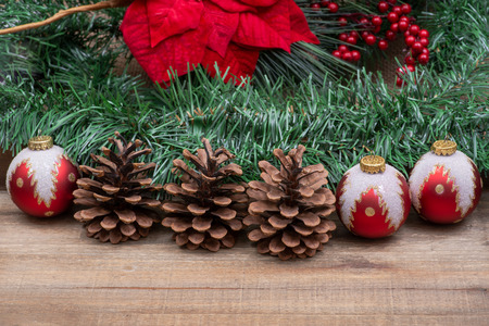 Winter holiday decoration: Blooming Red Poinsettia, Pine, Berry bush, Christmas tree balls, pine cone on wooden background. Standard-Bild