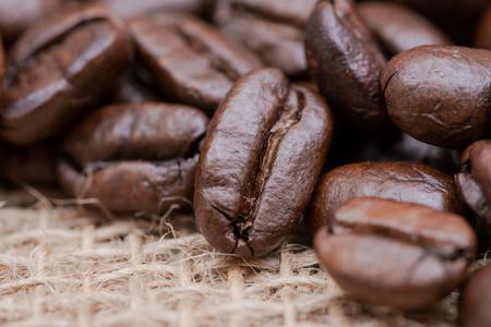Macro shot of whole bean organic smooth medium dark roast coffee from Sumatra on burlap background.