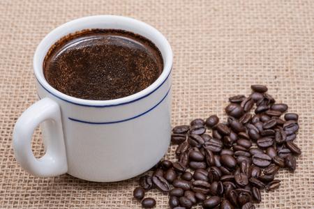 Cup of turkish brewed and whole bean organic smooth medium dark roast coffee from Sumatra on burlap background.