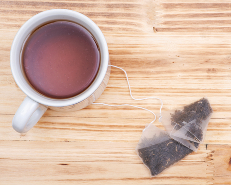 Cup and pyramid pouches of organic whole leaf earl grey tea on wooden background.