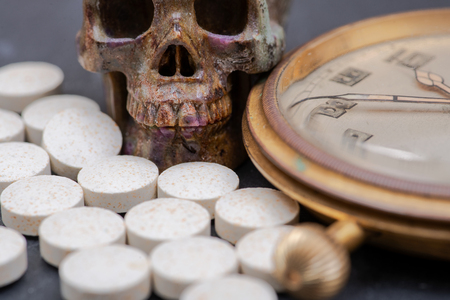 Concept for whom the bell tolls: antique pocket watch, carved skull and medical pills on natural stone background. Stockfoto