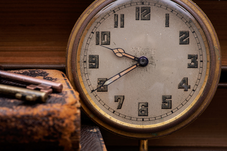 Panta rhei concept: Antique pocket watch, vintage keys and pile of old books on natural cork background.