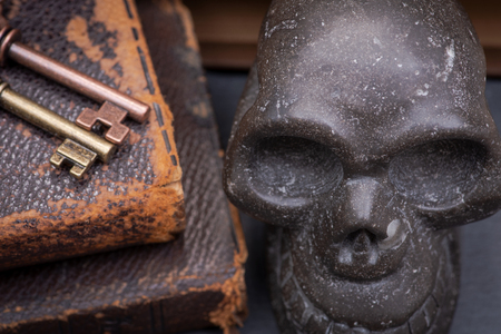 Pile of antique hard cover books, old vintage metallic keys and carved skull on natural stone background