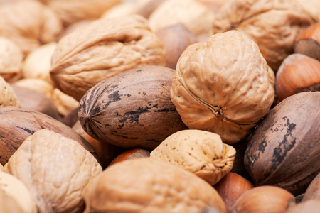 Macro shot of different nuts: almond, walnut, hazelnut and pecan on burlap background.