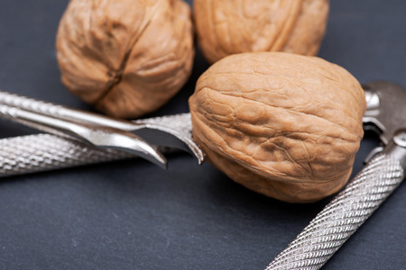Brown premium raw organic walnuts and nutcracker on natural stone background Stock Photo