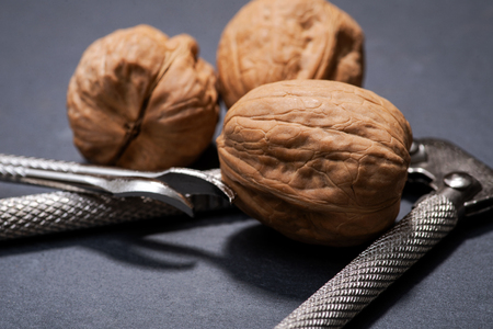 Brown premium raw organic walnuts and nutcracker on natural stone background Banque d'images