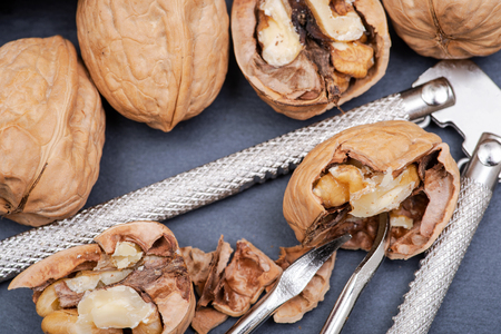 Brown premium raw organic walnuts and nutcracker in wooden bowl on natural stone background