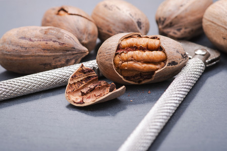 Fresh organic pecans nuts and stainless steel nutcracker on natural stone background.