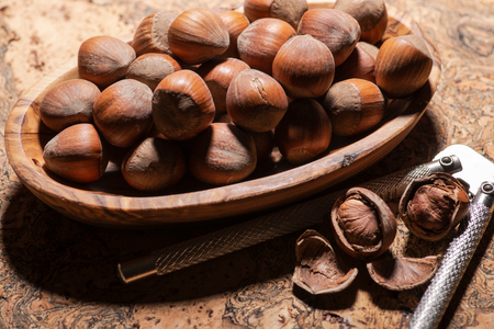 Fresh organic high quality hazelnuts, filberts and stainless steel nutcracker on natural cork background.
