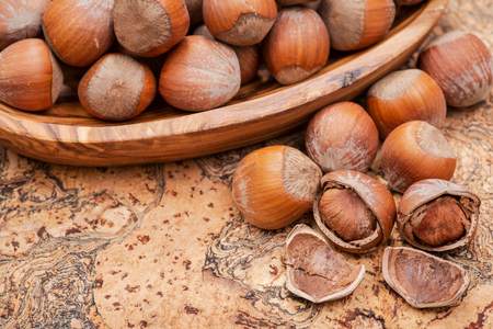 Fresh organic high quality hazelnuts, filberts in wooden bowl on natural cork background.