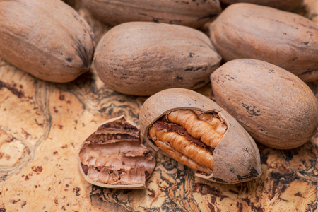 Fresh organic pecans nuts in wooden bowl on natural cork background.