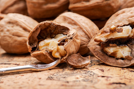 Brown premium raw organic walnuts and nutcracker on natural cork background. Banque d'images