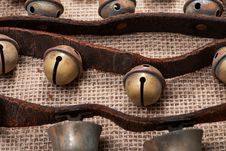Antique vintage oxidize brass sleigh bells on leather strap and burlap background