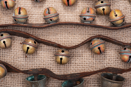 Antique vintage oxidize brass sleigh bells on leather strap and burlap background Reklamní fotografie - 114424331