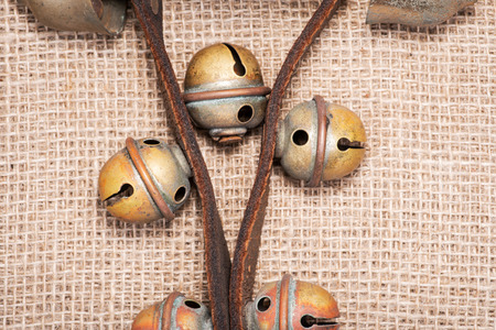 Antique vintage oxidize brass sleigh bells on leather strap and burlap background Reklamní fotografie - 114424349