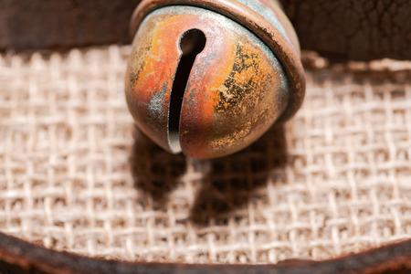 Antique vintage oxidize brass sleigh bells on leather strap and burlap background Reklamní fotografie - 114424379