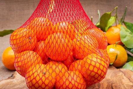 Fresh ripe organic mandarins in plastic mesh sack on olive wood and burlap background.
