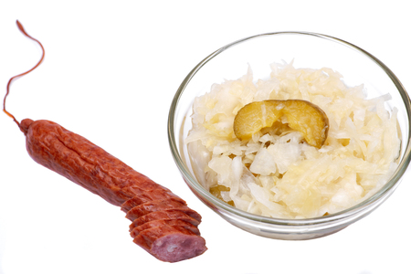 Traditional organic raw and fermented sauerkraut with pickled Persian cucumbers and grass fed beef smoked sausage stick isolated on white background.