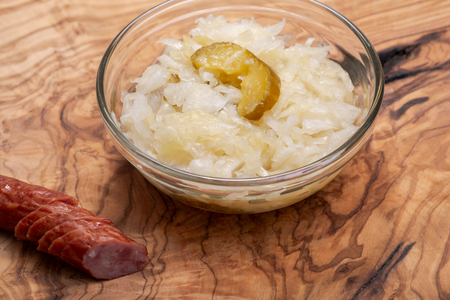 Traditional organic raw and fermented sauerkraut with pickled Persian cucumbers and grass fed beef smoked sausage stick