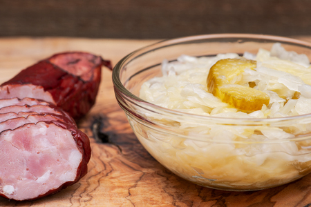 Traditional organic raw and fermented sauerkraut with pickled Persian cucumbers and homemade smoked pork sausage