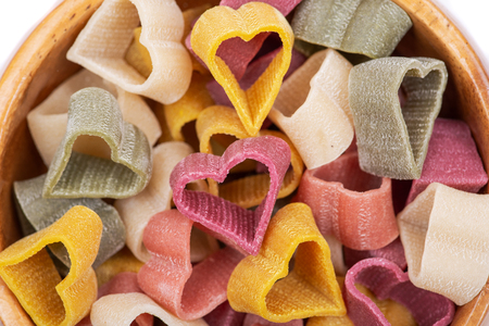 Durum wheat semolina heart-shaped 5 flavors pasta with vegetables in wooden bowl. Valentine's Day.