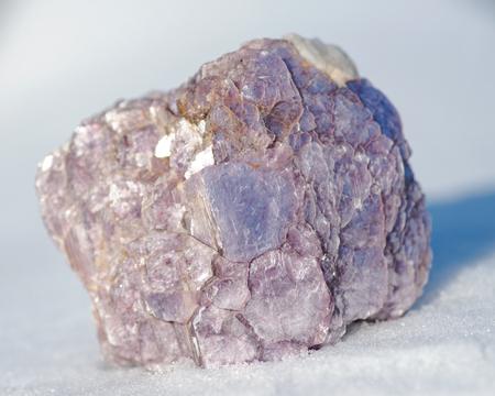 Rough Purple Lepidolite cluster from Brazil on white snow at a sunny winter day. Lepidolite Mica Slices. Reklamní fotografie