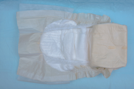 Extra large size briefs for adults isolated on blue under pad. Diapers for adults.