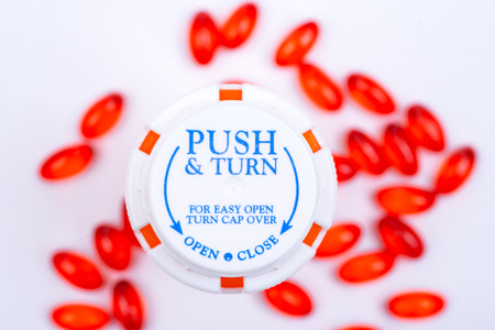 Docusate sodium red capsules and plastic container with Child-Resistant Push&Turn Cap. Top view.
