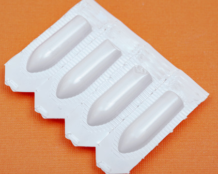 Medication in disposable plastic suppository moulds on orange background. Rectal drug administration
