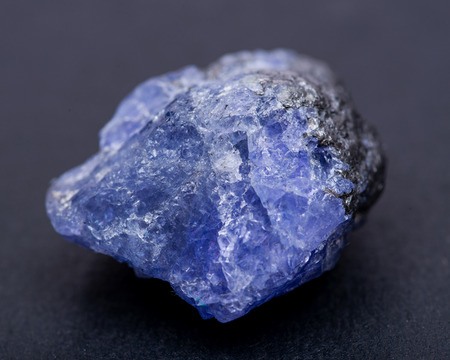 Soft blue violet rough TANZANITE from Tanzania isolated on black background.
