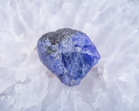 Soft blue violet rough TANZANITE from Tanzania placed on a crystalline druzy center of  Polished Large Natural Blue Lace Agate slab from Brazil.