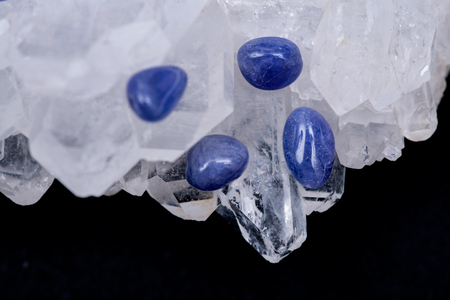Soft blue violet TANZANITE extra quality beads from Tanzania on FADEN QUARTZ CLUSTER. Isolated on black background.