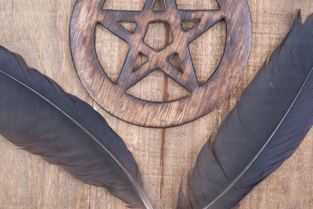 Two Black Raven feathers and Wooden encircled Pentagram symbol on wood background. Five elements: Earth, Water, Air, Fire, Spirit.