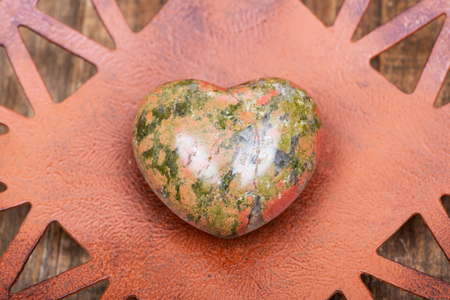 Highly polished puffy Unakite Heart from Unakas Mountains in North Carolina, on Rustic Orange decorative plate.