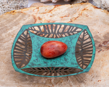 Hand polished Carnelian stone from Brazil on copper green decorative plate.