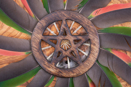 Wooden encircled Pentagram symbol in the middle of a circle made of colorful parrot feathers. Five elements: Earth, Water, Air, Fire, Spirit. Stockfoto