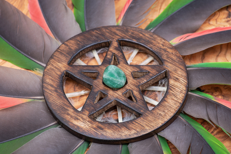 Wooden encircled Pentagram symbol with Green Aventurine in the middle of a circle made of colorful parrot feathers. Five elements: Earth, Water, Air, Fire, Spirit.